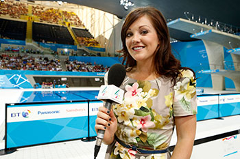 Woman holding microphone next to swimming pool
