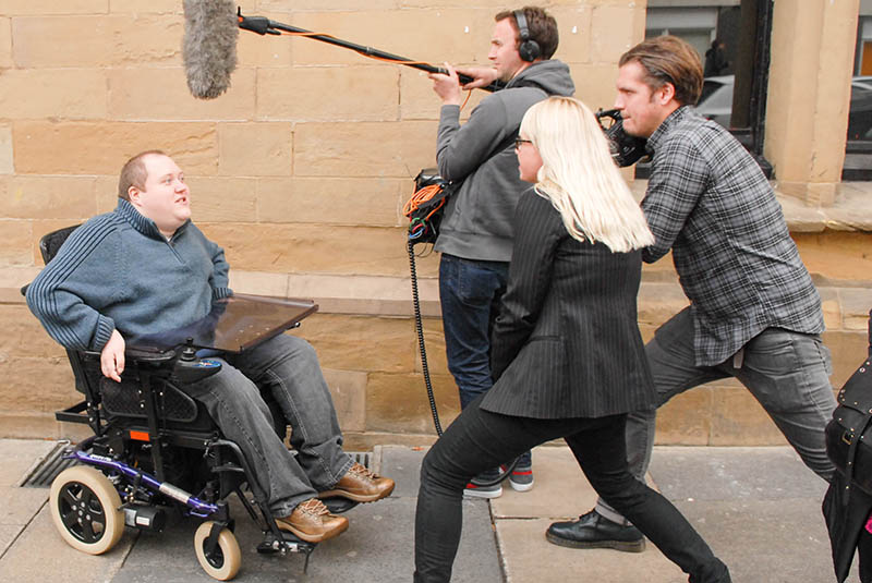 A man in a wheelchair being interviewed for television