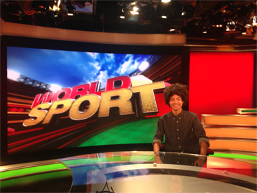 Man sitting in front of a screen which says World Sport